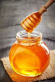 Honey pouring into jar Royalty Free Stock Photo