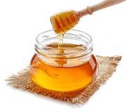 Honey pouring into jar Royalty Free Stock Photos