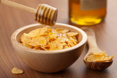 Honey pouring over cornflakes Royalty Free Stock Images