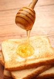 Honey pouring over toast bread Stock Photo