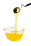 Honey pouring from the spoon. Thick sweet honey pouring from the spoon and into the small honey pot Stock Photo