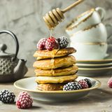 Pancakes with raspberries and blackberries. Honey pours on the drain of pancakes on a plate with raspberries and blackberries next to cups and a kettle on a gray Royalty Free Stock Image