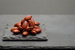 Honey roasted almonds. Piled on a gray slate snack plate Royalty Free Stock Image