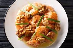 Honey Shrimp stekas med en tempurasmet och kastas snabbt i en honungsås och en sötad valnötnärbild horisontal?verkant arkivbild