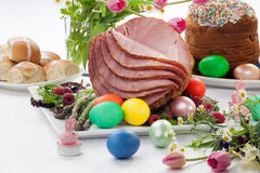 Honey Sliced Ham For Easter. Whole baked honey sliced ham with fresh raspberry, asparagus, dyed Ester eggs, Easter cake, and cross buns. Spring flowers Royalty Free Stock Photos