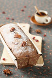 Honey and Spice Loaf Cake. With candied fruit and pecans on a wooden cutting board, with a cup of coffee Royalty Free Stock Photos