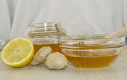 Honey and spices on a wooden surface. Honey in a jar and in a glass bowl with a wooden dipper on a wooden base, next to lemon and ginger Stock Photos