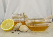 Honey and spices on a wooden surface. Honey in a jar and in a glass bowl with a wooden dipper on a wooden base, next to lemon, ginger and cloves Stock Photo