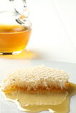 Honey comb and honey. A honey comb and a jar of honey on the background Royalty Free Stock Photo