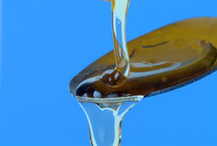Honey on a Spoon. Honey pouring into a spoon on blue background stock photo