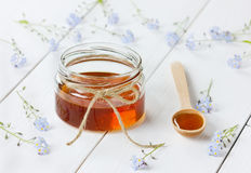 Honey in a spoon and jar decorated forget-me-not flowers Stock Photos