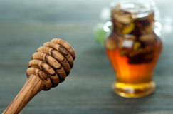 Honey spoon and jar with nuts on a wooden table Stock Photos