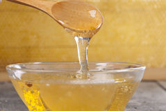 Honey with a spoon on the wooden table. Close up Stock Images