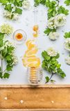 Honey stains from jar with flowers and honey comb on white background Stock Photos