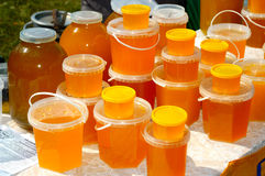 Honey Stall. Jars with amber-coloured fresh honey Royalty Free Stock Photography