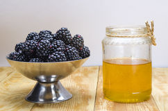 Honey with a stick and blackberry stock photo