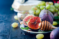 Honey stick and figs. Honey stick, Ripe purple figs and mint on dark slate board on wooden background Stock Photos
