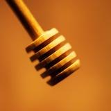 Honey stick over golden honey background close up. Stock Images