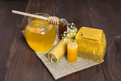 Honey still life with liquid honey and beeswax. Honey still life with three type of liquid honey, wax and beeswax candle on the wooden table decorated with small royalty free stock photo