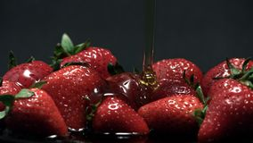 Honey and strawberries 4K 120fps. Honey Pours on Strawberries in slow motion 4K 120fps on dark background stock footage