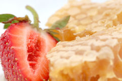 Honey and strawberry. Piece of honey and strawberry close-up Royalty Free Stock Image
