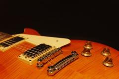 Honey sunburst electric guitar closeup on black background. Shallow depth of field. Royalty Free Stock Photography