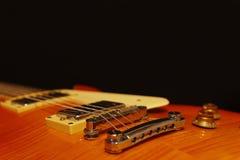 Honey sunburst vintage electric guitar closeup on black background, with plenty of copy space. Selective focus. Stock Photography