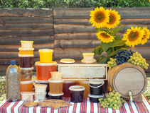 Honey and sunflowers. Still life with different honeys and honeycombs,blossom dust,sunflowers,grape and keg of mead on table with wooden fence as background Royalty Free Stock Image