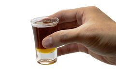Honey syrup in shotglass in hand holding on isolated white background. Honey syrup in shot glass in hand holding on isolated white background royalty free stock photos