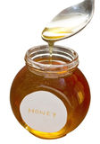 Honey. Taking out of the container with spoon.  on white, with clipping path Royalty Free Stock Photo
