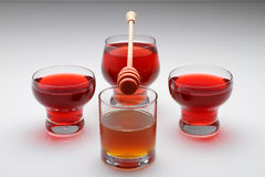 Honey and Tea. Three red tea glass on the table with honey Stock Photo