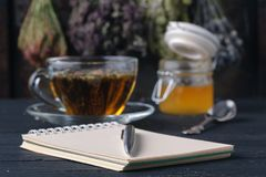 Honey with tea on rustic table backgound with herbs Stock Photos