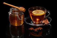 Honey and tea with spices and lemon. Honey in glass pot  and cup of tea with ginger, cinnamon, anise and lemon on a black background Royalty Free Stock Photography