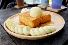 Honey Toast with Banana and Vanilla Ice Cream on Wooden Salver. Close Up Bread Buttered Toast with Whipped Cream Dessert on Wood D. Ish Background Great for Any Royalty Free Stock Images