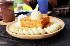 Honey Toast with Banana and Vanilla Ice Cream on Wooden Salver. Close Up Bread Buttered Toast with Whipped Cream Dessert on Wood D. Ish Background Great for Any Stock Image
