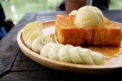 Honey Toast with Banana and Vanilla Ice Cream on Wooden Salver. Close Up Bread Buttered Toast with Whipped Cream Dessert on Wood D. Ish Background Great for Any Stock Images