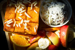Honey toast with fresh fruit on wooden plate. Royalty Free Stock Photography