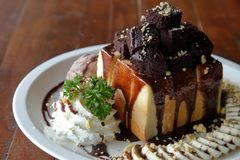 Honey toast ice cream with banana sliced and whipped cream top with brownie served on white plate over wooden table royalty free stock photos