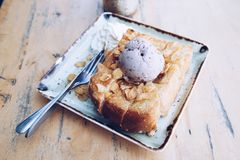 Honey toast and ice cream. Honey toast and blueberry ice cream with almond topping sprinkle honey on wood table in cafe or restaurant Royalty Free Stock Photo