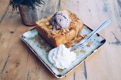 Honey toast and ice cream. Honey toast and blueberry ice cream with almond topping sprinkle honey on wood table in cafe or restaurant Royalty Free Stock Images