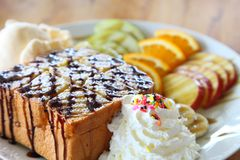Honey toast ice cream with mix fruit sliced and whipped cream served on white plate over wooden table royalty free stock photos