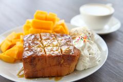 Honey toast served as dessert with peeled decorative fresh mango with latte coffee on dark brown wooden table stock photos