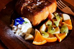 Honey toast Topped with condensed milk with Mixed Fruit. On wood table royalty free stock image