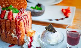 Honey toast topping with strawberries, a side of whipped cream, vanilla ice cream. Bread toast on white dish on blurred background. Of chocolate lava cake royalty free stock photo