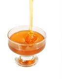 Honey in a vase. Dense honey flows in a glass vase Royalty Free Stock Image