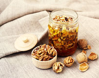Honey with walnuts in a glass jar, walnut kernels in a wooden bowl and the whole walnuts Royalty Free Stock Image