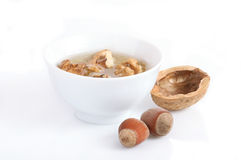 Honey walnuts and hazelnuts. Honey walnuts on a white background Royalty Free Stock Photography