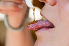 The honey which is flowing down in a mouth of the beautiful girl Royalty Free Stock Photos
