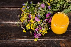 Honey, wild flowers and spoon on wooden background. Free space for your text. stock photography