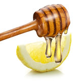Honey with wood stick pouring onto a slice of lemon. Stock Image